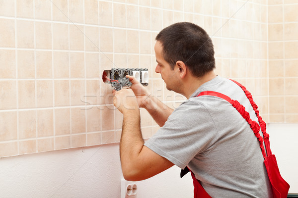 Electrician installing electrical wall fixture Stock photo © lightkeeper