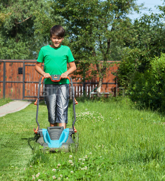 Young boy cutting the grass with a lawn mower Stock photo © lightkeeper