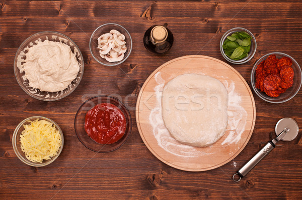 Phases of making a pizza - stretching the dough on wooden plate Stock photo © lightkeeper