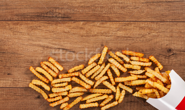 French fries spilled on the table from paper holder - copy space Stock photo © lightkeeper
