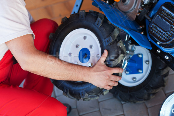 Man mounting tyre on a gasoline motor  tiller Stock photo © lightkeeper