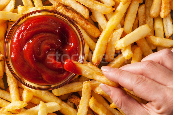 Hand dipping french fries in tomato sauce or ketchup Stock photo © lightkeeper