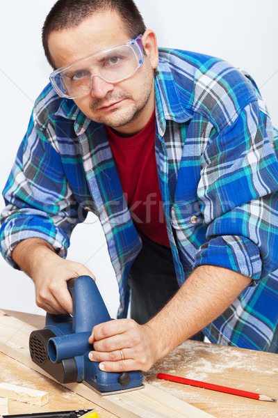 Carpenter or joiner working with electric planer Stock photo © lightkeeper