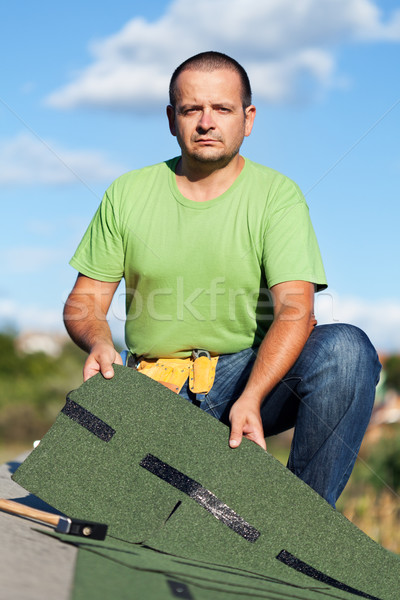 Worker holding  bitumen roof shingles on top of building Stock photo © lightkeeper