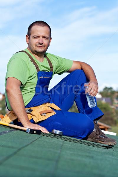 Worker laying bitumen roof shingles Stock photo © lightkeeper