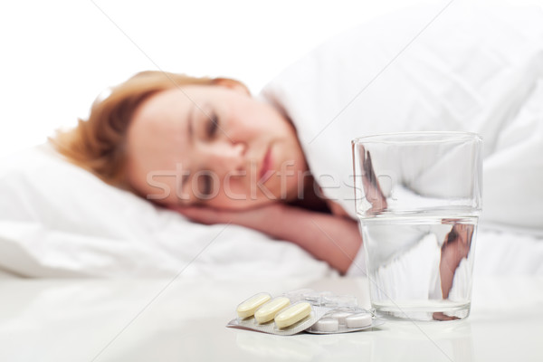Stock photo: Woman fighting sickness with pills and resting