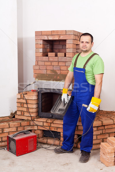 Worker mounting the door of a brick masonry heater Stock photo © lightkeeper