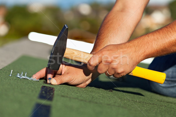 Man hands fastening bitumen roof shingles Stock photo © lightkeeper