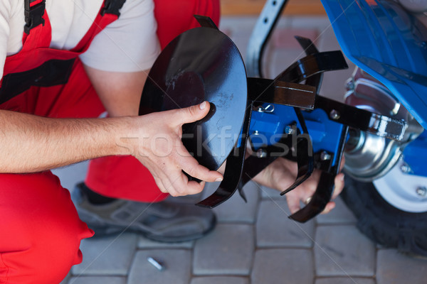 Worker mounting tilling accessory on a cultivator machine Stock photo © lightkeeper