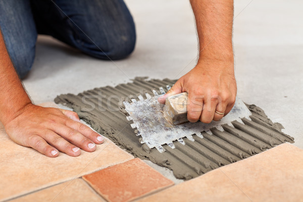 Worker hands spreading adhesive for ceramic floor tiles Stock photo © lightkeeper