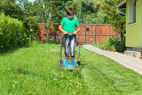 Boy cutting grass around the house in summertime Stock photo © lightkeeper