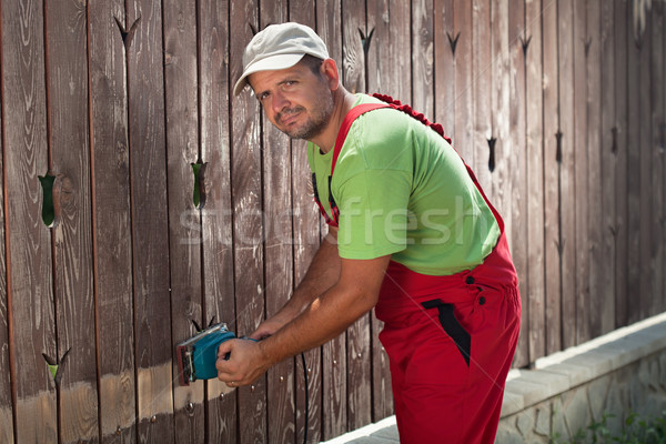 Worker using electric sander to remove old paint Stock photo © lightkeeper