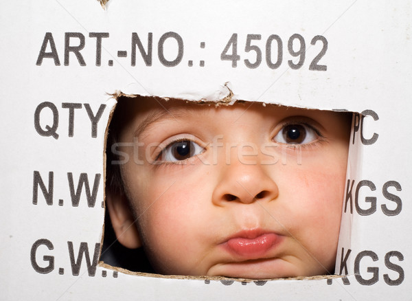 Bored kid peeking out from a cardboard box Stock photo © lightkeeper