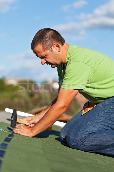 Man on the roof fastening bitumen roof shingles Stock photo © lightkeeper