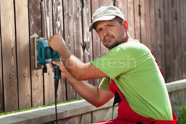 Worker polishing old wooden fence with power tool - a vibrating  Stock photo © lightkeeper