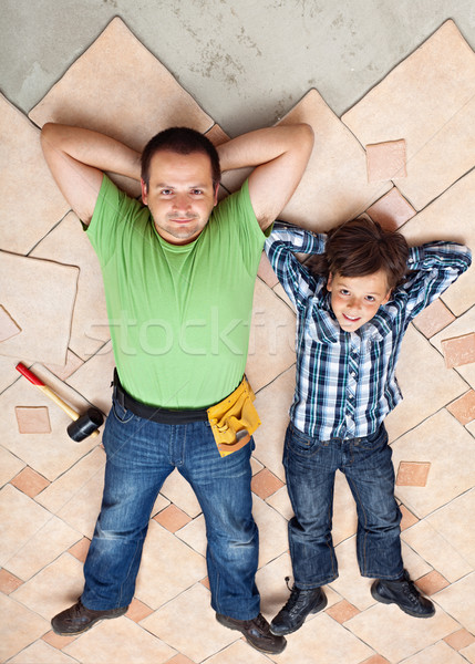 Father and son resting on unfinished floor tiles surface Stock photo © lightkeeper