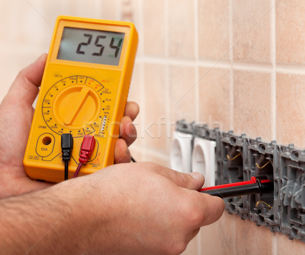 Electrician hands measuring voltage in electrical wall socket wi Stock photo © lightkeeper