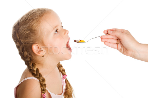 Drug abuse - little girl taking pills with spoon Stock photo © lightkeeper
