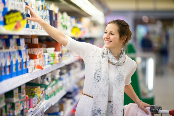 Stock photo: Beautiful young woman shopping for diary products