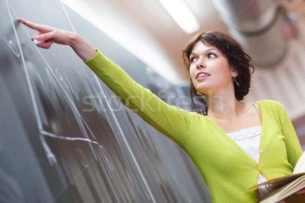 Pretty young  teacher writing on the chalkboard Stock photo © lightpoet