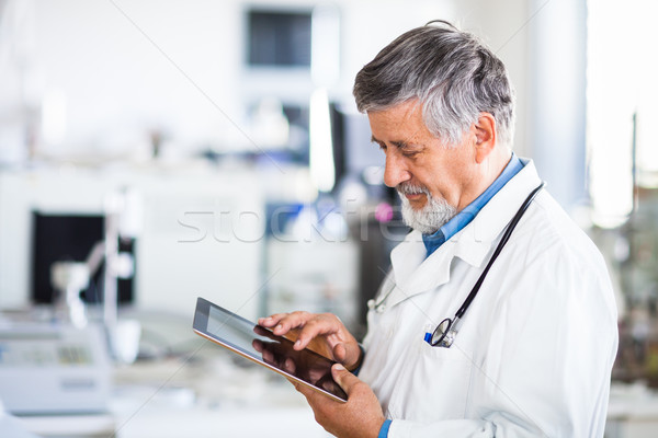 Senior doctor using his tablet computer at work  Stock photo © lightpoet