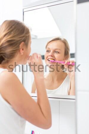 Pretty female brushing her teeth in front of mirror  Stock photo © lightpoet