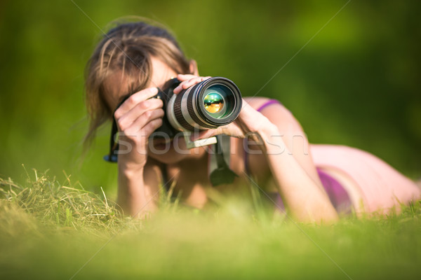 Pretty female photographer lying in grass Stock photo © lightpoet