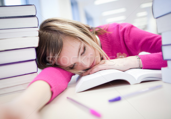Stock photo: in the library - very tired/exhausted, pretty, female student