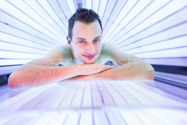 Yakışıklı genç rahatlatıcı modern solaryum Stok fotoğraf © lightpoet
