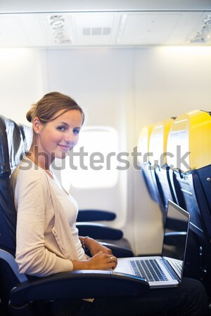 Young woman working on her laptop computer on board of an airpla Stock photo © lightpoet