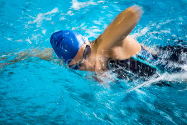 Female swimmer in an indoor swimming pool - doing crawl Stock photo © lightpoet