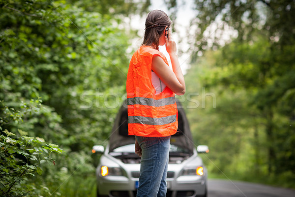 Young female driver wearing a high visibility vest, calling the roadside service Stock photo © lightpoet
