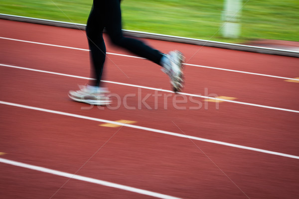 Young woman running at a track and field stadium (motion blurred Stock photo © lightpoet