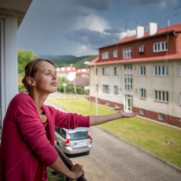 Csinos fiatal nő esik az eső erkély piros fiatal Stock fotó © lightpoet