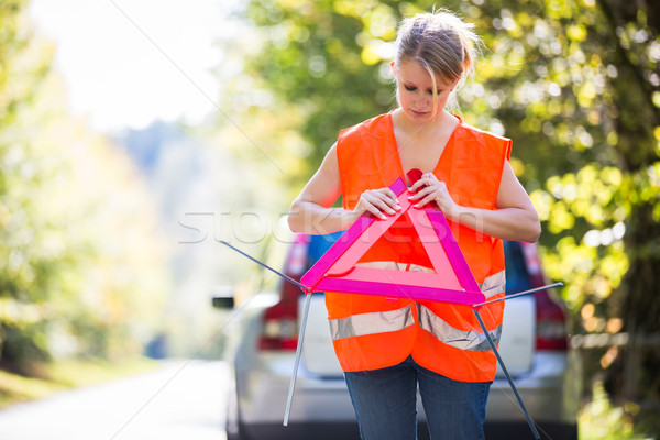 Young female driver wearing a high visibility vest, setting up t Stock photo © lightpoet