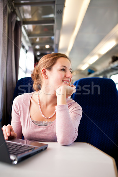 Young woman using her laptop computer while on the train  Stock photo © lightpoet