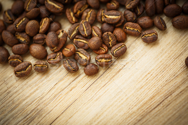 Stock photo: Coffee beans on a wooden desk lit by warm light (shallow DOF; co