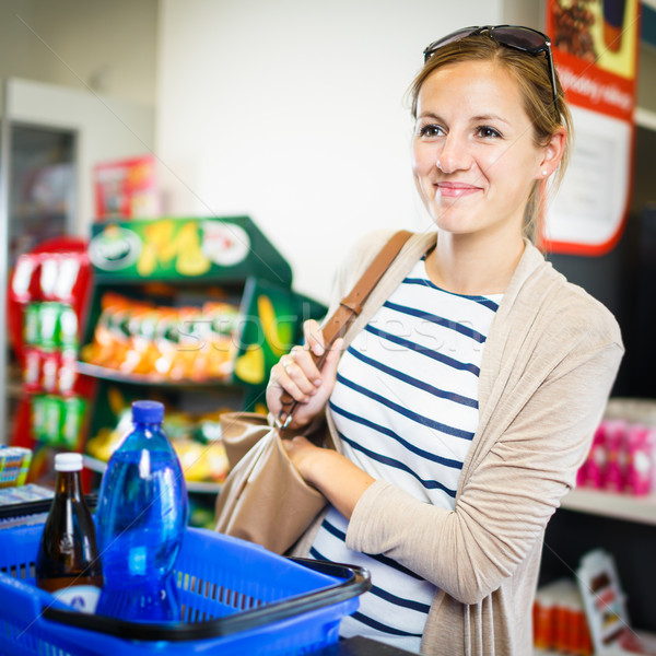 Beautiful young woman paying for her groceries at the counter of Stock photo © lightpoet