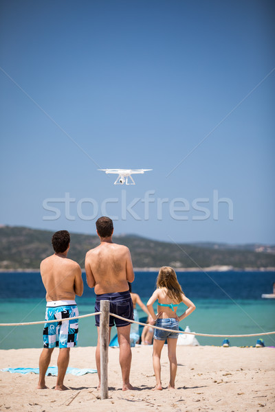 Young people flying a drone by remote control on a beach/sea Stock photo © lightpoet
