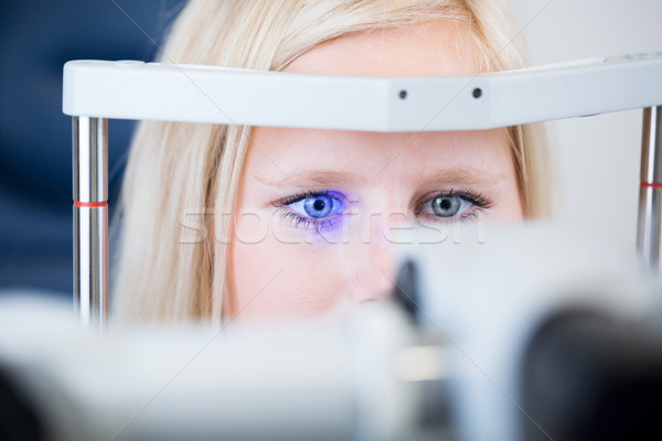 Pretty, young female patient having her eyes examined by an eye doctor Stock photo © lightpoet