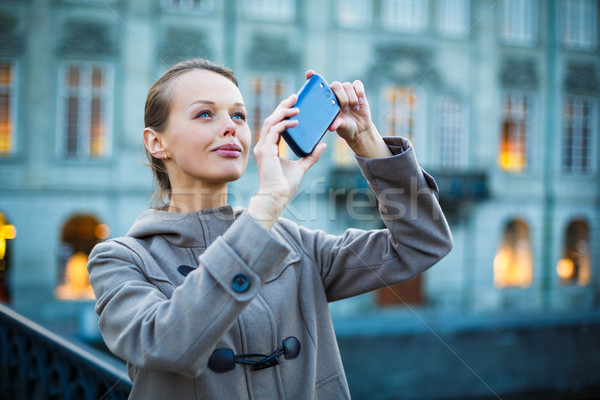Elegant, young woman taking a photo with her cell phone camera Stock photo © lightpoet