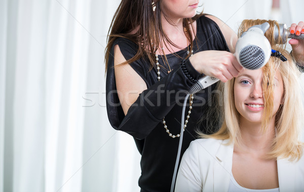Hairdresser/Hairstyle artist working on a young woman's hair Stock photo © lightpoet