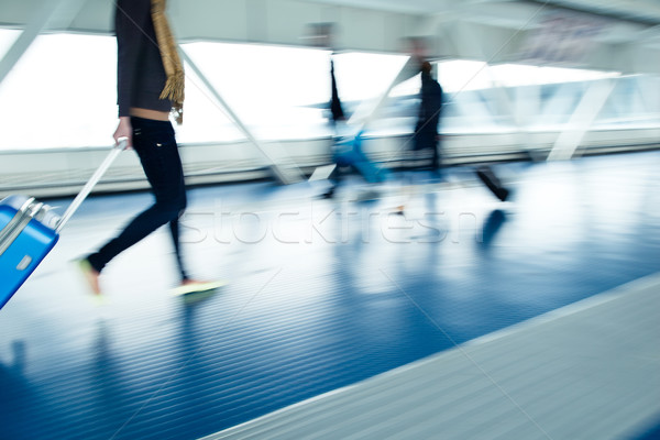 Stock photo: Airport rush: people with their suitcases walking along a corrid