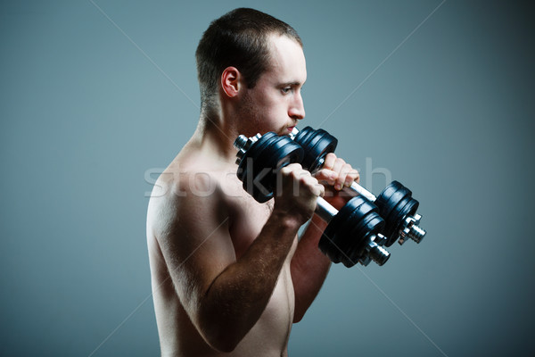 Close up of young man lifting weights over grey background (colo Stock photo © lightpoet