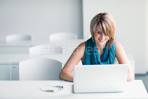 Pretty, young woman at an office, using a laptop and her smartphone Stock photo © lightpoet