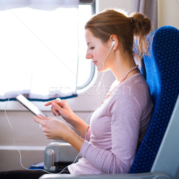 Stock photo: Young woman using her tablet computer while traveling by train