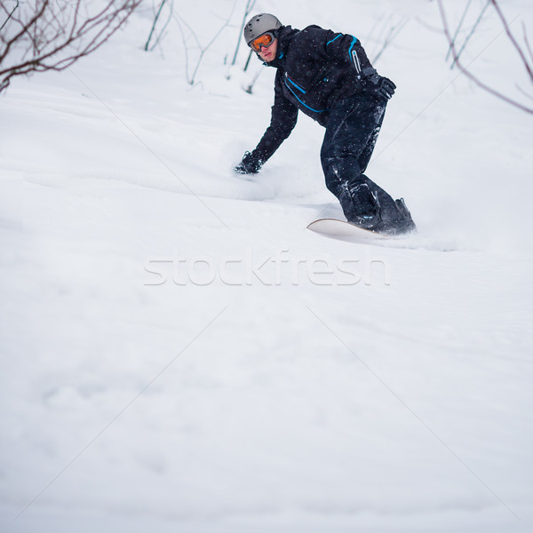 Young man freeride snowboarding off-piste in a mountain resort   Stock photo © lightpoet