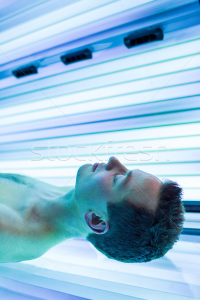 Handsome young man relaxing during a tanning session in a modern Stock photo © lightpoet