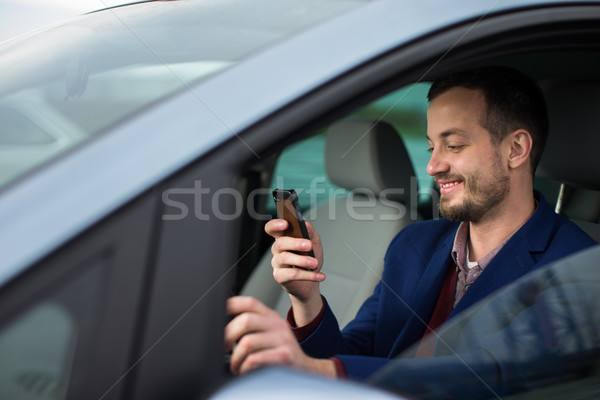 Handsome young man looking at his cellphone  Stock photo © lightpoet