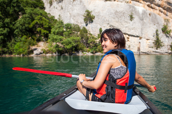Pretty, young woman on a canoe on a lake, paddling Stock photo © lightpoet